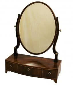 An oval mahogany and holly wood strung toilet mirror