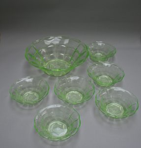 A serving bowl and six dessert bowls made from pale green glass