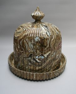 An Agateware cheese stand and cover